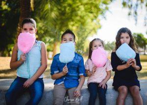 sesión de foto de 4 hermanos con algodones de azúcar azul y rosa