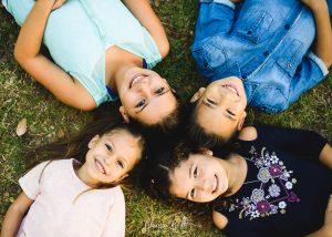 foto de 4 hermanos tirados en el pasto con sus cabezas juntas formando una semicruz